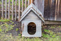 Old wooden doghouse. Homemade doghouse from wooden boards with rusty iron chain Royalty Free Stock Photos