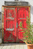 Old wooden door. Frontal view of an old wooden door painted in red Royalty Free Stock Image