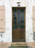 Old wooden door. An old wooden door on a white wall in France Stock Image