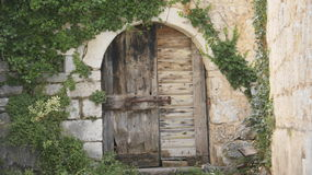 Old wooden door. In the old stony wall Stock Photos