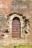 Old wooden door in aged brick wall Stock Photography