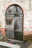 Old wooden door. Aged brick wall. Enter the ancient castle Stock Image