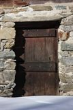Old wooden door. Old door of an alpine house in Gran Paradiso National Park, Aosta Valley, Italy Royalty Free Stock Photography