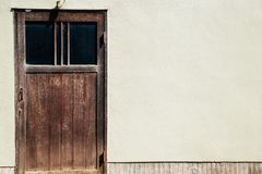 Old wooden door and wall in Kyoto, Japan. Old wooden door and beige wall in Kyoto, Japan stock images