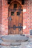 Old wooden door. With brick arch facade Stock Photography
