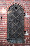 Old wooden door. With brick arch facade Stock Image