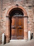 Old wooden door with brick archway. Old wooden door with upper railing and brick archway Stock Photos
