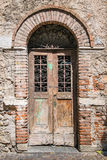 Old wooden door with brick archway. Old wooden door with upper railing and brick archway Royalty Free Stock Image