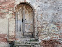 Old wooden door in old brick wall.  Stock Photos