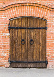 Old wooden door. In a brick wall Stock Photos