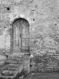 Old wooden door in old brick wall. Black and white photo.  royalty free stock images