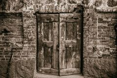 Old wooden door in a brick wall. With lock Royalty Free Stock Photo