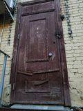 Old wooden door in a brick wall. Old weathered wooden door in a brick building with a doorbell Stock Images