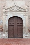 Old wooden door in a brick wall. A photo of an old wooden door in a brick wall Stock Image