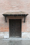 Old wooden door in a brick wall Stock Images