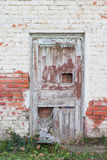 Old wooden door. In a brick wall walled Royalty Free Stock Image