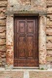 Old wooden door. Of a broken brick wall Stock Photo