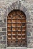 Old wooden door. Of a broken brick wall Royalty Free Stock Image