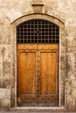 Old wooden door. Of a broken brick wall Royalty Free Stock Images