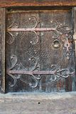 Old wooden door with carved metal handle Royalty Free Stock Photos