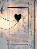 Old wooden door with a carved romantic heart Stock Images
