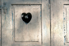 Old wooden door with a carved romantic heart Royalty Free Stock Photo