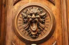 Old wooden door with carving in the form of the head of a monster with an open mouth royalty free stock images