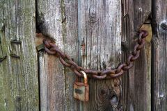 Old wooden door and chain forgotten in time. stock image
