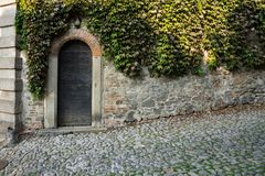 Wooden door in city wall in Monselice, Italy royalty free stock image