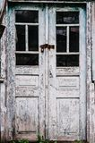 Old wooden door closed on the lock. Peeling paint. Closed on hin stock images