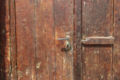 Old wooden door dark red color and old iron lock fragment royalty free stock image