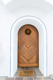 Old wooden door decorated by Christmas wreath Royalty Free Stock Photo
