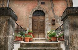 Old wooden door decorated with flowerpots from the medieval town. Old wooden door decorated with flowerpots and steps from the medieval town, Tuscany, Italy stock photo