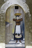 Old wooden door decorated with a painting of woman in the old ci Stock Image