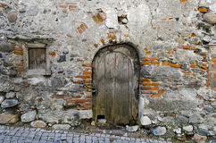 Old wooden door in a desolate wall Stock Photography