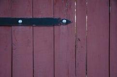 Old wooden door detail. Arrow-like metal decoration on an old wooden door with cracks Stock Image