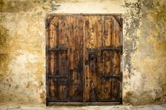 Old wooden door at the courtyard entrance of a traditional sands. Old wooden door enforced with rivets at Mdina, Malta Stock Photos