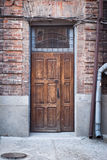 Old wooden door. Entrance to the brick house Stock Photos
