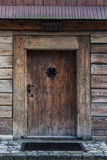 Old wooden door. The wooden entrance and the door to the church. Modest decorated with wrought-iron door handle of a window in the middle protected by wrought Stock Image