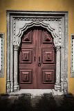 Old wooden door framed by a carved stone. tinted Royalty Free Stock Photography