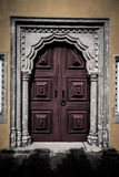 Old wooden door framed by a carved stone. tinted Stock Photos