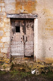 An old wooden door. An old French weather beaten bleached wooden door in a stone wall royalty free stock photography