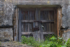 Old wooden door or gate and metal wires of the rusted lock. Outside the house, village, everything comes into disrepair Royalty Free Stock Image