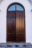 Old wooden door with glass in ancient building Stock Images