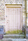 Old wooden door with grating in a brick wall Stock Photography