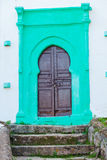 Old wooden door. On a green painted wall Stock Images