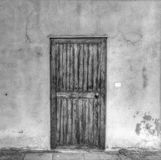 Old wooden door in a grunge wall in black and white Royalty Free Stock Photography