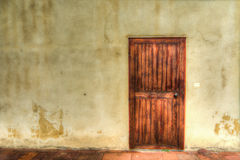 Old wooden door in a grunge wall Royalty Free Stock Photo