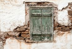 Old wooden door on grunge weathered wall. Old wooden window with green shutters on weathered wall stock images