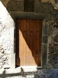 Old wooden door in half sun and half shade. An ancient door set in grey stone in half sun and half shade with cobbled pathway royalty free stock photos